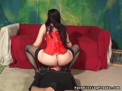 Dominatrix in red corset posing and sitting on slave's face Thumb