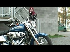 Red-haired biker in appealing striptease Thumb