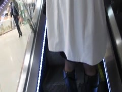 Chick in black stockings witn red tops on escalator Thumb